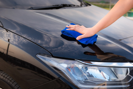 Close up portrait of womans hand cleaning her car.