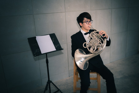 Portrait of musicain playing instrument horn in the hall.