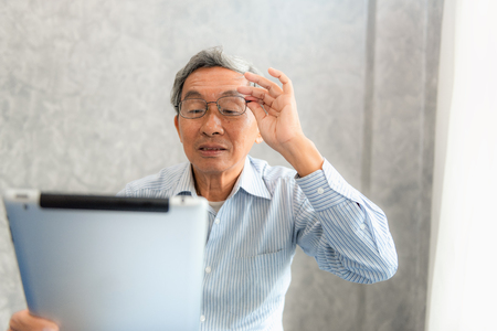 Senior man having eyesight problems while he is using a tablet. Stock Photo