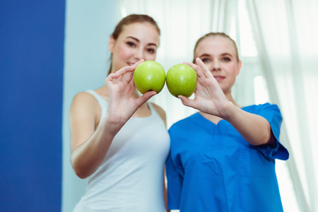Portrait of female nutritionist and patient are holding a green apple and showing healthy vegetables and fruits,, healthcare and diet concept.