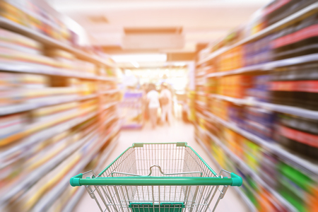 Shopping trolley in department store with goods shelf background., Abstract motion blurred concept.