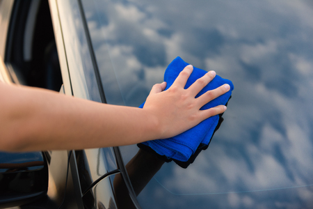 Closeup womans hand cleaning front hood a car., Car care and maintenance concept. Stock Photo