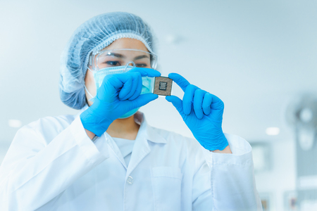 Portrait of electronics engineer is holding CPU's computer for examination. Imagens