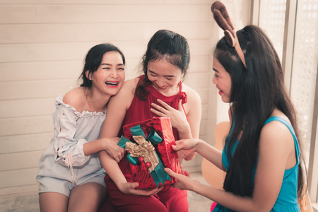 Portrait of asian woman surprising her friend with a Christmas gift.