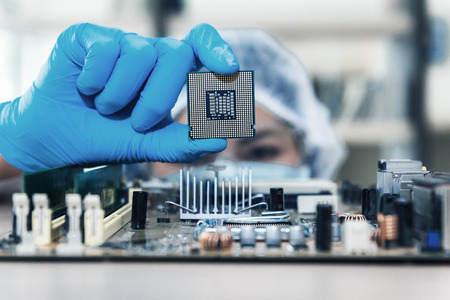 Closeup of computer technician researcher is holding CPU's computer for examination before replacing into curcuit mainboard.