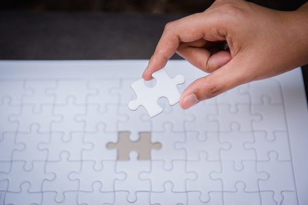 Closeup of woman hands fulfill the last piece of jigsaw puzzle to complete.,Business solutions, success mission concept. Standard-Bild - 112058821