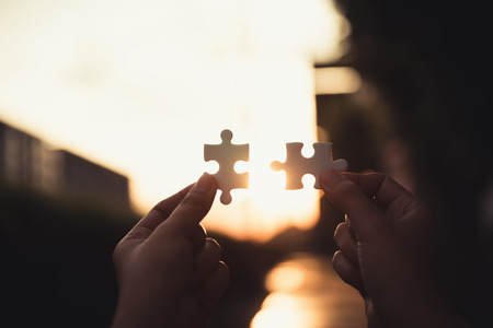 Closeup of woman hands connecting jigsaw puzzle on sunset scene, Business solutions, success mission concept. Standard-Bild - 112058937