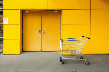 Shopping cart in front of emergency fire exit door and aluminum composite wall of department store.