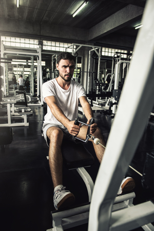 Handsome man is rowing exercise with bodybuilder machine in fitness club.,Portrait of strong man doing working out calories burning in gym., Healthy and fitness sport gym concept. 写真素材