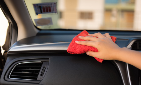 Closeup woman hand is washing and cleaning with microfiber at console panel inside a car., Car maintenance service and transportation concept.