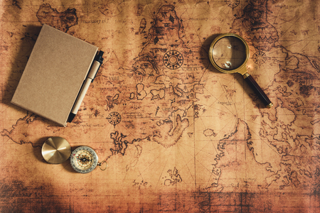La navegación explora la planificación del viaje con la lupa de la brújula y el diseño del cuaderno en el fondo del mapa del mundo., Las expediciones investigan el concepto de tesoro o destino de viaje. Foto de archivo