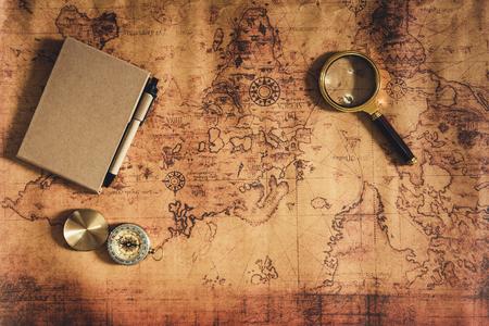 La navigazione esplora la pianificazione del viaggio con la lente d'ingrandimento della bussola e il layout del taccuino sullo sfondo della mappa del mondo., Le spedizioni indagano sul concetto di tesoro o destinazione di viaggio. Archivio Fotografico