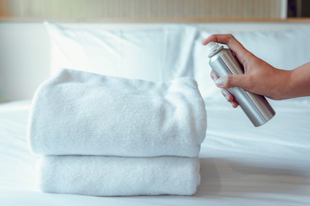 Woman Hand is Spraying Air Freshener to Towels in Bedroom, Unpleasant smell and Aromatherapy Concept. Фото со стока