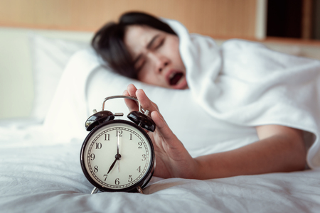 Turning off Sound or Snoozing The Alarm Clock Concept, Beautiful Woman Waking Up in The Morning at Bedroom While Her Hand is extending Alarm of Timer Clock. Banco de Imagens
