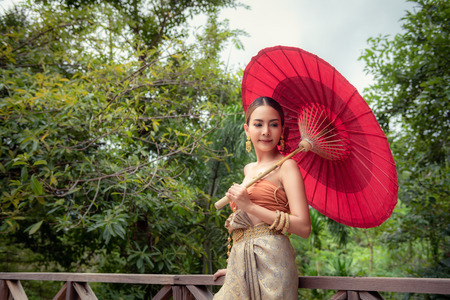 Portrait of Beautiful Thai Woman in Traditional Clothing While Holding Red Umbrella., Pretty of Thai Girl is Wearing Vintage Clothes and Outdoor Standing Posing., Heritage of Art, Thailand.