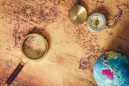 Nawigacja Eksploracja planowania podróży., Cel podróży i plan wyprawy Wyjazd wakacyjny., Zbliżenie na układ lupy, kompas, model globalny na tle mapy świata.