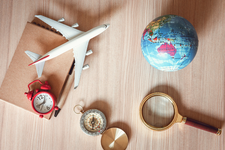 Navigation Explore of Journey Tourism Planning., Travel Destination Plan for Vacation Trip., Top View of Layout Magnifying Glass, Pocket Watch, Compass, Airplane and Global Model on a Wooden Table.