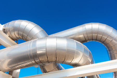 Cooling Chiller or Steam Pipeline and Insulation of Manufacturing in Oil and Gas Industrial, Petrochemical Distribution Pipe at Refinery Plant. Overhead Steel Piping Isolated Blue Sky Background.