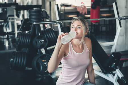 Beautiful Fitness Woman is Drinking Water From Bottle After Working Out in Gym, Portrait of Athletic Pretty Woman is Drinking Water After Exercising in Front of Bodybuilder Machine, Sport and Healthy.