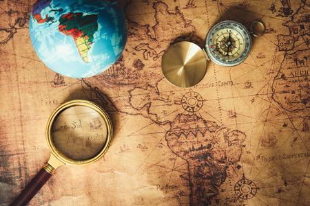 Nawigacja Poznaj planowanie podróży. Cel podróży i plan wyprawy Wyjazd wakacyjny. Zbliżenie na układ lupy, kompas na tle mapy świata. Zdjęcie Seryjne
