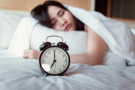 Bastante joven está durmiendo y despertador en el dormitorio, hermosa chica está durmiendo en su cama y se relaja por la mañana. Foto de archivo