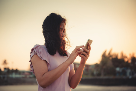 Portrait of Woman is Using Smartphone at The Beach During Sunset, Asian Tourist is Relaxing With Her Cell Phone on The Beach in Holiday Time. Technology Communication Concept. 写真素材