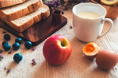 Homemade and Breakfast Food With Hot Milk, Whole Wheat Bread, Apple, Kiwi Fruit and Parboiled Egg on a Table, Delicious Menu in The Morning, Healthy Eating Concept.
