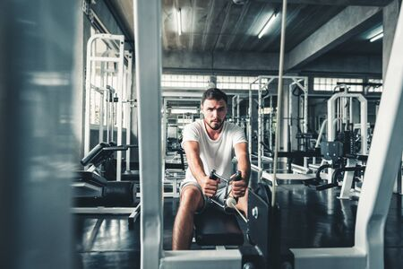Handsome Man is Exercising With Bodybuilder Machine in Fitness Club.,Portrait of Strong Sporty Man Doing Working Out Calories Burning in Gym., Healthy and Fitness Sport Lifestyle Concept. Фото со стока