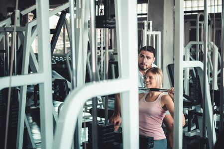 Beautiful Woman is Exercised Training With Bodybuilder Machine in Fitness Club., Attractive of Sporty Girl Doing Working Out With Her Trainer in Gym, Healthy and Sport Exercising Lifestyle Concept. Фото со стока