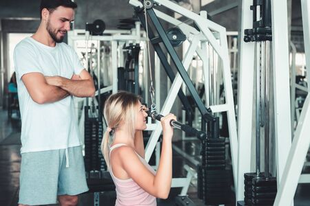 Portrait of Beautiful Woman is Exercised Training With Bodybuilder Machine in Fitness Club., Attractive of Sporty Girl Doing Working Out With Her Trainer in Gym, Healthy and Sport Lifestyle Concept.