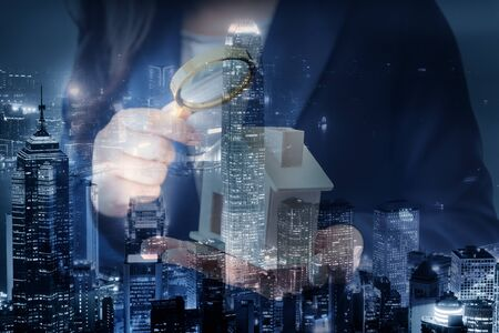 Business Real Estate and Residential Investment Concept, Broker Sell Agency of Property Estates Investigation By Magnifying Glass for Searching New Housing on Cityscape Background. Double Exposure