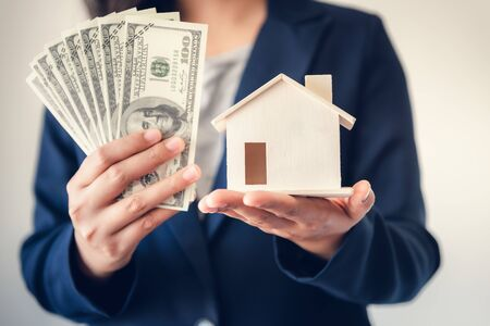 Business Real Estate and Residential Investment Concept, Broker Sell Agency of Property Estates Showing Money and House Model to Customer. Business Financial Banking Stock Investing