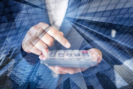 Business Accountant Woman Using Calculator for Calculating Financial Investment Tax Income and Profit Estimate, Double Exposure of Businesswoman Hands is Holding Calculator With Cityscape Background