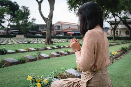 Close-Up of Religious Christian Woman Hands Clasped While Honoring and Praying to Military in War Cemetery. Teenager Woman in Expression Sadness and Pray for Soldier Prisoner of War in Tomb. 版權商用圖片