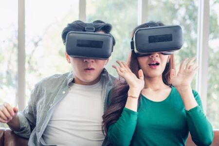 Young Couple Having Fun While Watching Video Via Virtual Reality Together. Couple Love Having Enjoyment With Electronic VR Goggles Gaming on Couch. Entertainment Innovation/Lifestyles Concept