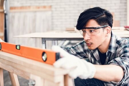 Carpenter Man is Working Timber Woodworking in Carpentry Shop, Craftsman is Leveling Alignment Timber Plank for Wooden Furniture in Workshop. Workmanship and Job Occupation Concept 写真素材