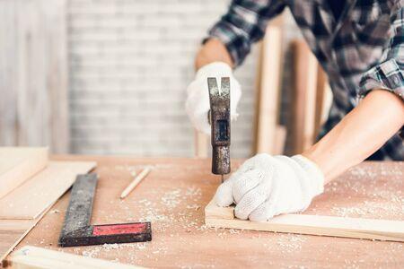Carpenter Man arbeitet Holzholzbearbeitung in der Schreinerei, Handwerker hämmert einen Nagel in den Holzrahmen für Holzmöbel in der Werkstatt. Verarbeitungs- und Beschäftigungskonzept