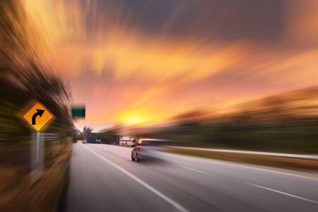 Bewegungsbewegung des Fahrzeugs im Transportmodus auf der Verkehrsstraße, Bewegungsunschärfe des Automobils während der Geschwindigkeit auf der Autobahn während der Sonnenuntergangsszene. Transport-Auto-Fahr- und Sicherheitskonzept