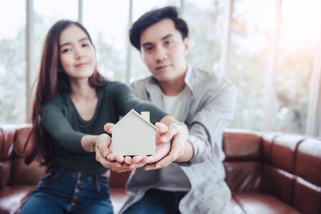 Couple Hands Holding Housing Model for Future Real Estate Saving, Attractive Asian Couple Hand Joint to Protection Home Property Togetherness. House Insurance and Residential Loan Investment Concept. Фото со стока