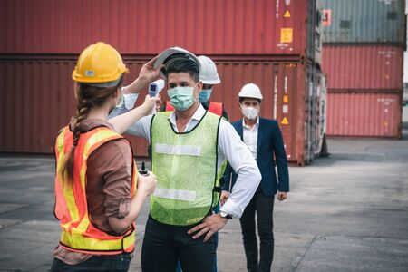 Coronavirus Covid-19 Disease Epidemic Crisis Situation, Container Shipping Worker Having Fever Body Scan by Thermometer Scanning at Ship Yard. Corona-Virus Covid19 Prevention of New Normal Concept