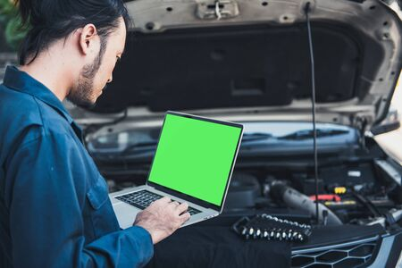 Mechanic Engineer is Diagnosing Car Engine and Electric Adjusting Transmission With Computer Laptop, Automobile Service Man Diagnostic Vehicle Car Engines Systems in Garage Workshop. Engineering Work