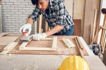 Carpenter Man is Working Timber Woodworking in Carpentry Workshops, Craftsman is Using Sander Machine on Timber Frame for Wooden Furniture in Workshop. DIY Workmanship, Job Carpenters Concept.