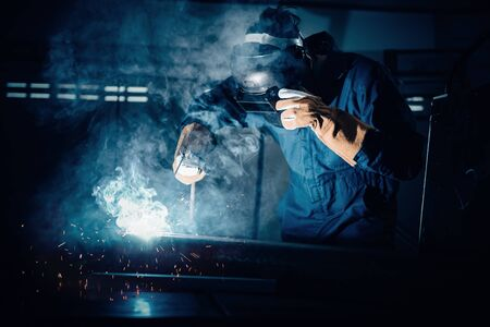 Technical Welder is Working Steel Welding in Assembly Workshop, Welder Structure in Safety Equipment is Welding Metal in Factory Assembling Production Line. Labor Skill and Construction Occupation