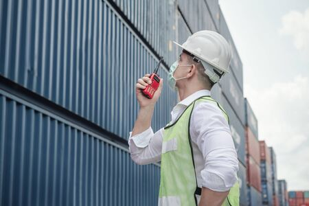 Transport Engineer Man Wearing Medical Face Mask for Prevention Coronavirus Epidemic Situation in Containers Logistic Shipping Yard. Transportation and Logistics after Coronavirus Covid-19 New Normal