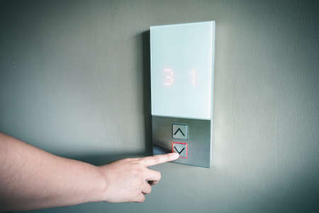 Closeup of Woman Hand is Pressing Elevator Button for Access to Office Building, Electrical Lift Buttons Control for Moving Up or Down Floor Level inside Buildings. Facility Electric Elevator Panel
