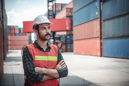 Portrait of Confident Transport Engineer Man in Safety Equipment Standing in Container Ship Yard. Transportation Engineering Management and Containers Logistics Industry, Shipping Worker Occupation 写真素材