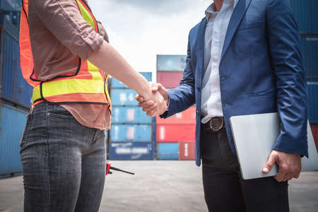 Businessman and Container Shipping Worker Handshake Together for Cooperation Shipment in Logistic Warehouse, Business Partnership Greeting Handshaking After Discussion Containers Transport Dealing.
