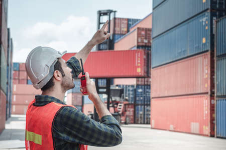 Container Logistics Shipping Management of Transportation Industry, Transport Engineer Managing Control Via Walkie Talkie in Containers Shipyard. Business Cargo Ship Import/Export Factory Logistic.