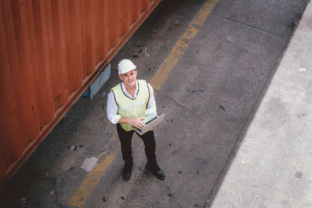 Container Shipping Logistics Engineering of Import/Export Transportation Industry, Transport Engineer is Controlling Management Containers Box on Laptop at Port Ship Loading Dock. Industrial Shipping Imagens