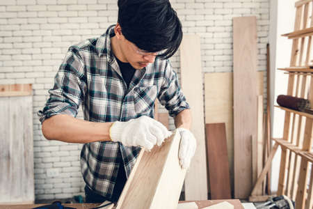 Carpenter Man is Working Timber Woodworking in Carpentry Workshops, Craftsman is Applying Glue to Timber Plank for Wooden Furniture in Workshop. DIY Workmanship, Job Carpenters Concept